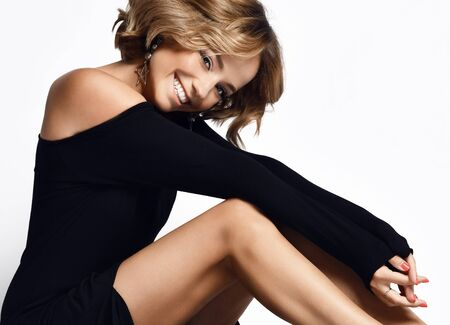 Closeup of emotional charmingly smiling woman with curly blonde hair sitting on the floor in off shoulder light black dress slipped off her knees exposing her thighs on white.