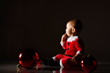 Photo pour Joyful infant baby boy toddler in santa costume is sitting surrounded by Christmas tree red balls, looking at copy space, reading, holding finger at mouth on dark background - image libre de droit