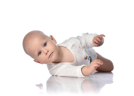 Photo for Infant child baby boy toddler in white bodysuit white shirt is lying on its side, trying to roll over, held out his hand on white background - Royalty Free Image