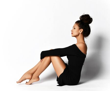 Sensual gorgeous woman curly brunette with fashion hairstyle in black tight evening dress is sitting sideways to us on the floor looking straight forward at copy space
