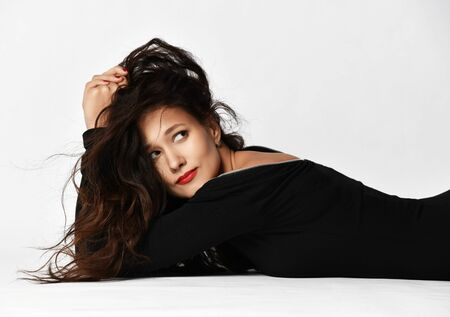 Portrait young sensual woman brunette with long curly hair in black dress is lying sexual posing on the floor looking up coquettishly flirty smiling