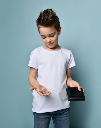 Little boy in white t-shirt showing empty wallet and few coins in hand over pastel blue background. Nothing to pay for housing no money concept. Difficult financial condition of people in crisis
