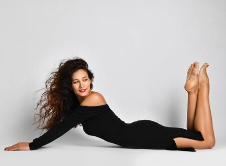 Woman with long curly brunette hair in black tight off-shoulder dress lies sexual posing on the floor with her bare feet up and looks back over background with copy space above