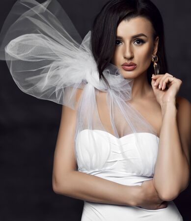 Photo pour Portrait of young beautiful brunette woman in white vintage dress with unusual decoration and earrings over dark background. Stylish event looks concept - image libre de droit