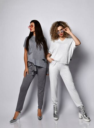 Photo pour Two young beautiful women in comfortable cotton costumes and stylish footwear standing over grey wall background. Beauty, fashion, trendy outfit concept - image libre de droit