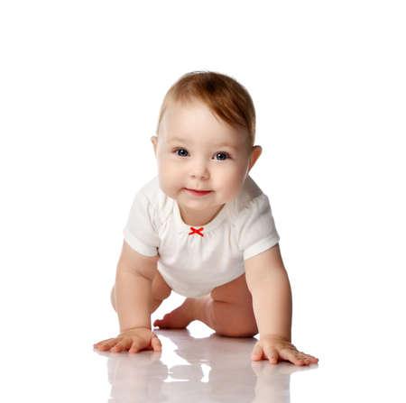 Foto de Adorable smiling curious little baby infant in white cotton bodysuit crawling creeping forward at camera over white background. Happy childhood concept - Imagen libre de derechos