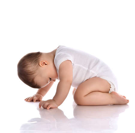 Photo pour Portrait of sweet cute baby boy toddler in white body barefoot crawling on floor and looking down at legs over white background in studio, side view. Happy infancy and babyhood concept - image libre de droit