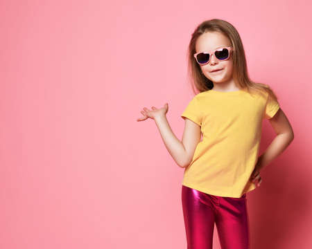 Photo for Smiling frolic kid girl in sunglasses, yellow t-shirt and leggings holds hand up with open palm as if she holds something on it over pastel pink background with free copy space - Royalty Free Image