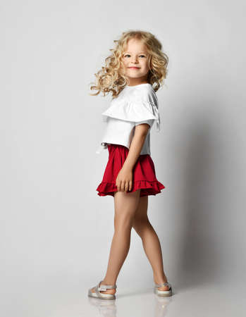 Photo pour Smiling blonde kid girl with curly hair in stylish casual clothing shorts and t-shirt standing posing back turned to us over grey wall background. Fashion for children concept - image libre de droit