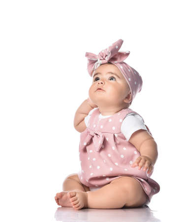 Photo for Thoughtful barefooted Infant baby toddler in polka dot dress and headband with bow sits on the floor looking up holding hand at head. Happy infancy and babyhood concept - Royalty Free Image