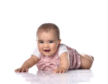 Photo pour Happy infant baby girl toddler in polka dot dress is lying on stomach on the floor with arms outstretched  tries to crawl. Happy infancy and babyhood concept - image libre de droit