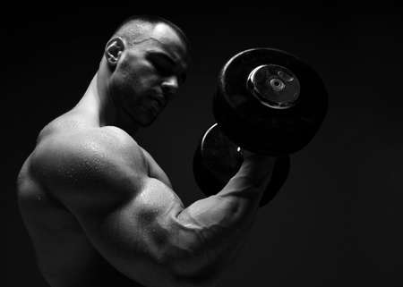 Photo for Portrait of muscular men, bodybuilder working out, lifting dumbbell, doing exercises for biceps looking at it - Royalty Free Image
