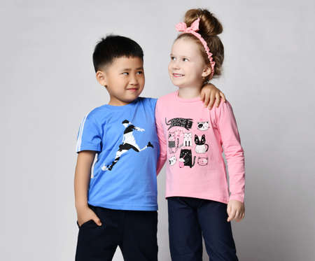 Photo pour Little cute Asian boy and blonde Caucasian girl in summer clothing best friends stand together hugging - image libre de droit