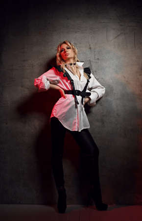 Photo pour Insolent blonde woman mistress in leather pants, white shirt with leather belts and cap stands at concrete wall - image libre de droit