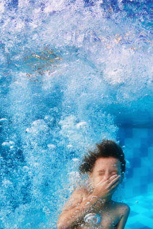 Photo for Amusing face portrait of smiling boy swimming and diving in blue pool with fun - jumping down underwater with splashes and foam. Family lifestyle and summer children water sports activity with parents - Royalty Free Image
