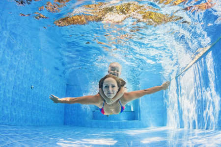 Happy family - positive mother with baby girl swimming and diving underwater with fun in outdoor pool. Healthy lifestyle, active parents, and people water sports activity on summer holidays with child