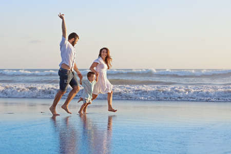 Foto de Positive family - father, mother with baby son hold hands and run  with fun along edge of sea on smooth sand beach. Active parents and people outdoor activity on tropical summer holidays with children - Imagen libre de derechos