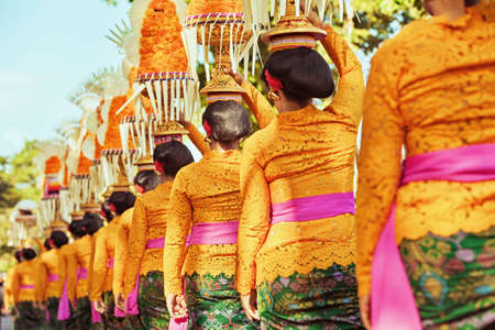 Procession of beautiful Balinese women in traditional costumes - sarong, carry offering on heads for Hindu ceremony. Arts festival, culture of Bali island and Indonesia people, Asian travel background