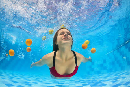 Young beautiful woman in bikini swimming and diving underwater in pool with fun for fresh citrus fruit. Active healthy lifestyle, water sport activity and relaxation on vacation in tropical spa resort