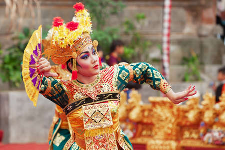 BALI ISLAND, INDONESIA - JUNE 28, 2015: Beautiful woman dressed in colorful sarong - Balinese style female dancer costume, dancing traditional temple dance Legong at Bali Art and Culture Festival show