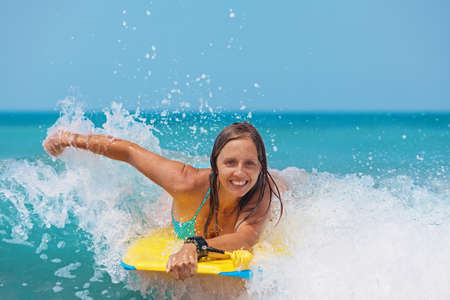 Photo pour Joyful young girl - beginner surfer with bodyboard has fun on small sea waves. Active family lifestyle, people outdoor water sport lessons and swimming activity on surf camp summer vacation with child - image libre de droit