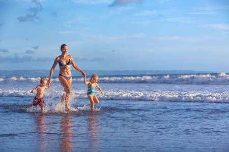Photo for Happy barefoot family having fun - mother, baby son, daughter together run with splashes by water pool along surf of sunset sea beach. Active parent and people activity on summer holiday with children - Royalty Free Image