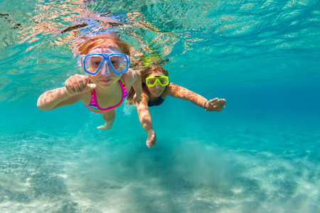 Photo pour Happy family - mother with baby girl dive underwater with fun in sea pool. Healthy lifestyle, active parent, people water sport outdoor adventure, swimming lessons on beach summer holidays with child - image libre de droit