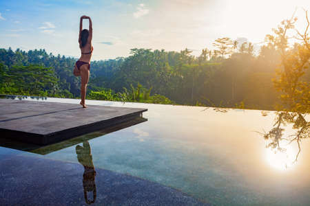 Foto de Good morning with yoga meditating on sunrise background. Active woman in bikini practicing on villa poolside to keep fit and health. Woman fitness training, sport activity on summer family holiday. - Imagen libre de derechos