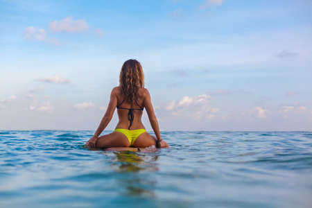 Happy girl in bikini have fun before surfing Surfer sit on surf board, look at sunset sky. People in water sport adventure camp, extreme activity on family summer beach vacation. Watersport background