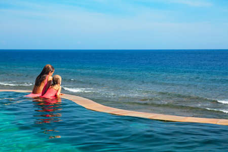Photo pour Happy family. Mother, baby daughter relax in luxury spa resort at poolside in infinity swimming pool with sea view. Travel lifestyle, recreation on summer beach vacation, kids water sports activity. - image libre de droit