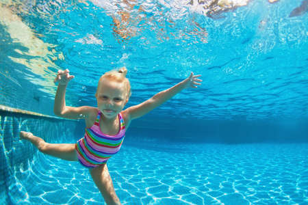 Photo pour Funny portrait of child learn swimming, diving in blue pool with fun - jumping deep down underwater with splashes. Healthy family lifestyle, kids water sports activity, swimming lesson with parents. - image libre de droit