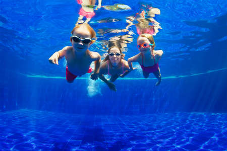 Photo pour Happy family - mother, baby son, daughter in goggles swim, dive in pool with fun - jump deep down underwater. Healthy lifestyle, people water sport activity, swimming lessons on holidays with kids - image libre de droit