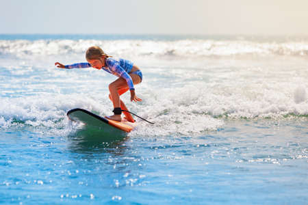 Happy baby girl - young surfer ride on surfboard with fun on sea waves. Active family lifestyle, kids outdoor water sport lessons and swimming activity in surf camp. Beach summer vacation with child.
