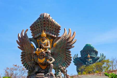 Foto de Landscape picture of old Garuda Wisnu Kencana GWK statues as  Bali landmark with blue sky as a background. Balinese traditional symbol of hindu religion. Popular travel destinations in Indonesia. - Imagen libre de derechos