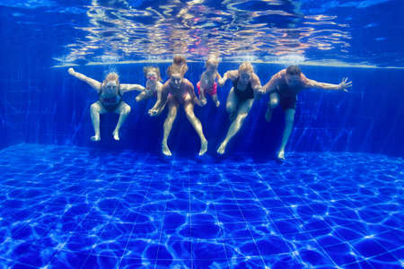 Photo pour Happy family in swimming pool. Smiling mother, children and grandparents swim, dive in pool with fun - jump deep down underwater. Healthy lifestyle, people water sport activity on holidays with kids - image libre de droit