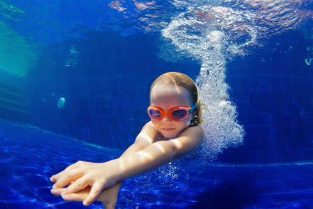 Photo for Happy family in swimming pool. Smiling child in goggles swim, dive in pool with fun - jump deep down underwater. Healthy lifestyle, people water sport activity, swimming lessons on holidays with kids - Royalty Free Image