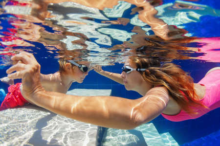 Happy family - mother, baby boy in goggles learn to swim and dive underwater with fun in swimming pool. Healthy lifestyle, active parents, people water sports activities on summer holidays with child.