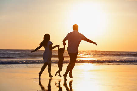 Foto für Happy family black silhouette on sun background. Father, mother, baby son run. Child jump with fun by water pool along sea surf on beach. Travel lifestyle, parents walking with kid on summer vacation. - Lizenzfreies Bild