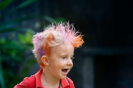 Foto de Funny portrait of boy with messy hairstyle. Crazy hipster kid. Stylish boy with painted colorful hair. Happy children having fun and celebrating at party in family summer camp. positive and cheerful. - Imagen libre de derechos