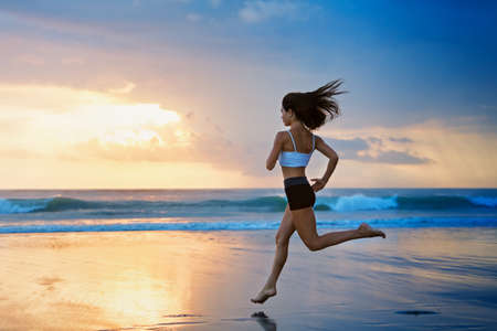 Photo pour Barefoot young girl with slim body running along sea surf by water pool to keep fit and burning fat. Beach background with blue sky. Woman fitness, jogging sports activity on summer family vacation. - image libre de droit