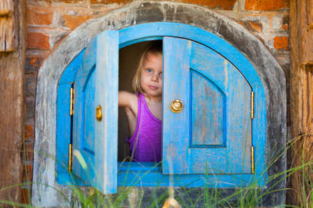 Photo pour Family funny holiday. Happy baby girl peek out of toy house window in yard garden. Summer healthy lifestyle, kids outdoor activity, educational games for preschooler, recreational adventure in park. - image libre de droit