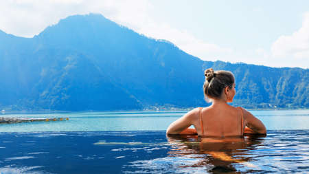 Photo pour Young woman relax in infinity pool with lake view. Natural hot spring spa under Batur volcano. Travel in Kintamani, Bali. Healthy lifestyle, recreational activity on family summer holiday. - image libre de droit