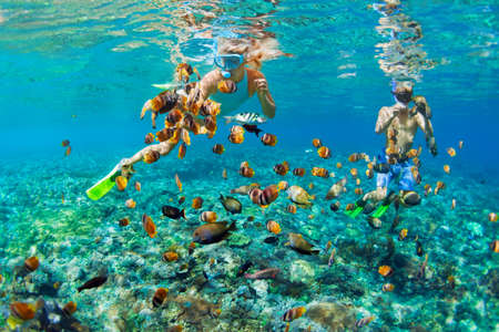 Photo pour Happy family vacation. Young couple in snorkeling mask hold hand, dive underwater with fishes in coral reef sea pool. Travel lifestyle, watersport adventure, swim activity on summer beach holiday - image libre de droit
