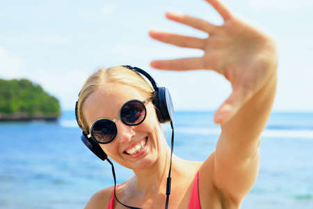 Photo pour Young positive girl in headphones and sunglasses listening music and dancing with fun at tropical beach party. Travel family lifestyle, recreational activities at summer cruise vacations. - image libre de droit