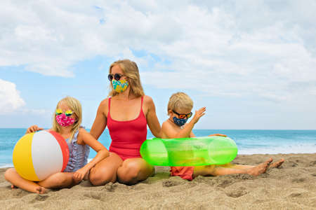 Photo pour Funny children in sunglasses, inflatable toys on tropical sea beach. New rules to wear cloth face covering mask at public places due coronavirus COVID 19. Family holidays with children, summer travel - image libre de droit