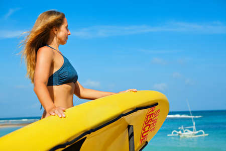 Photo for Life saving yellow board with surf rescue sign. Young lifeguard woman stand on duty, look at blue sea. Swimming people safety. Summer family vacation on ocean beach. Travel background. - Royalty Free Image