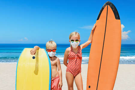 Photo pour Funny kids with surf boards wear protective mask on sea beach. Cancelled cruises, tours due coronavirus COVID 19 world epidemic. Travel ban for family vacation, tourism industry crisis at summer 2020 - image libre de droit