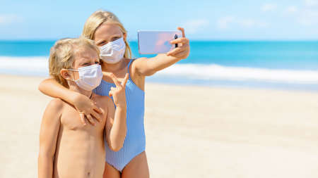 Photo pour Funny kids taking selfie photo by smartphone on tropical sea beach. New rules to wear cloth face covering mask at public places due coronavirus COVID 19. Family holidays with children, summer travel. - image libre de droit
