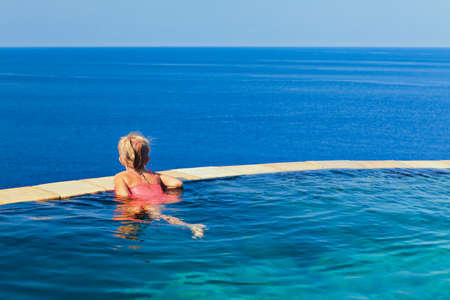 Photo pour Happy girl have fun on summer beach holiday. Young girl relaxing at edge of infinity swimming pool with sea view from hill top. Healthy family lifestyle, summer travel with kids on tropical islands. - image libre de droit