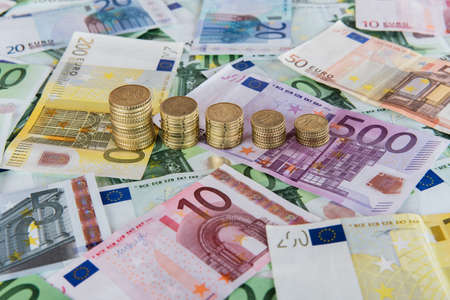 Euro banknotes and euro coins in simple example of falling euro prognoses.